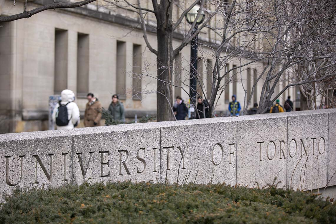 "stone signage that reads ""university of toronto"" at the intersection of st. george st and college st in toronto"