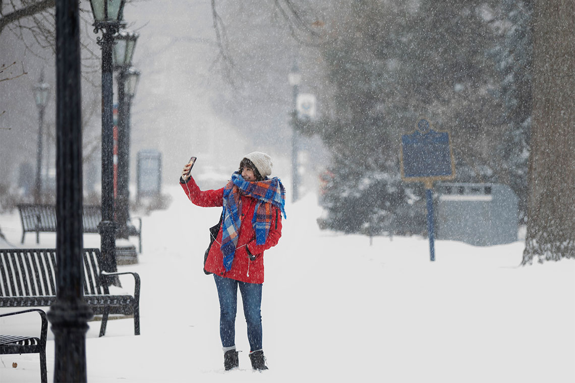 A woman take a selfie at the downtown U of T campus during a snowstorm