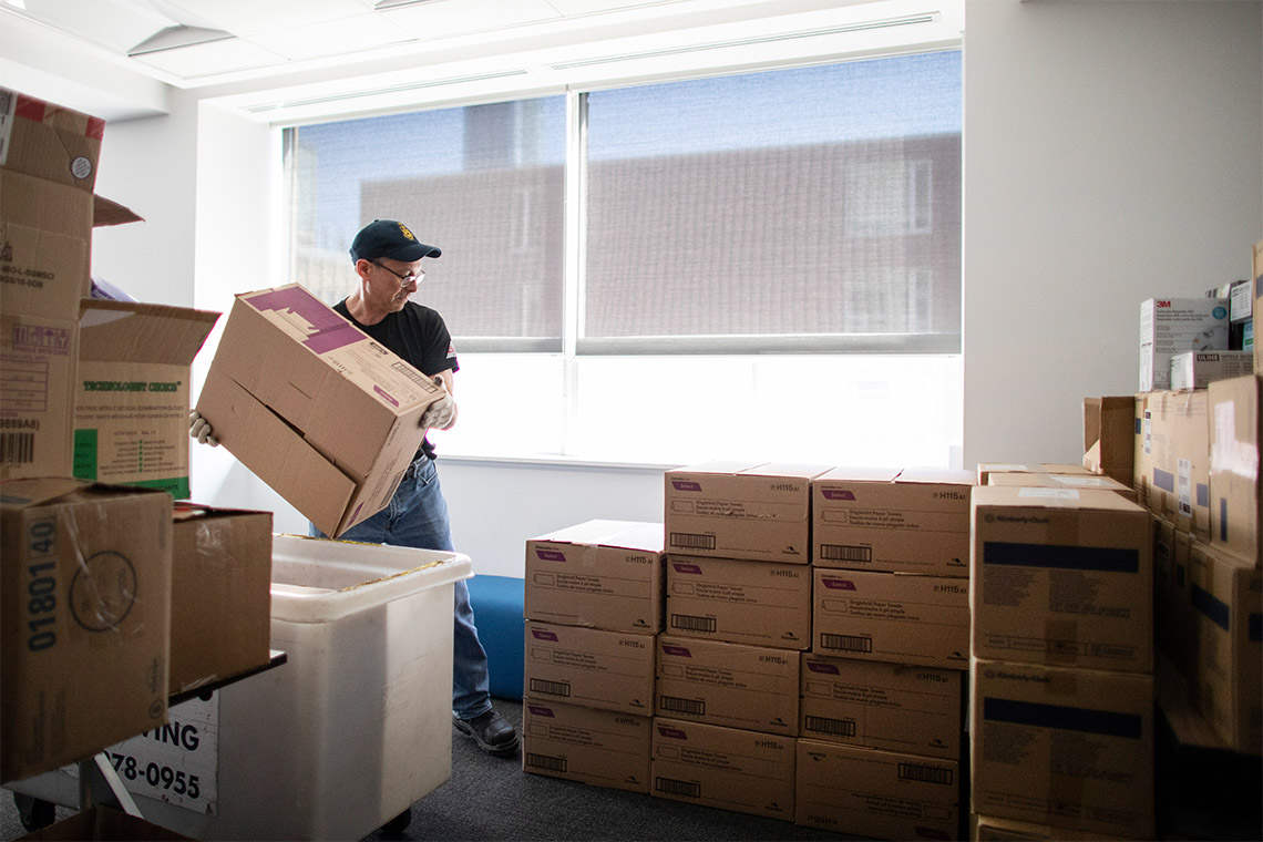 A worker lifts boxes of personal protective equipment supplies amidst stacks of other boxes