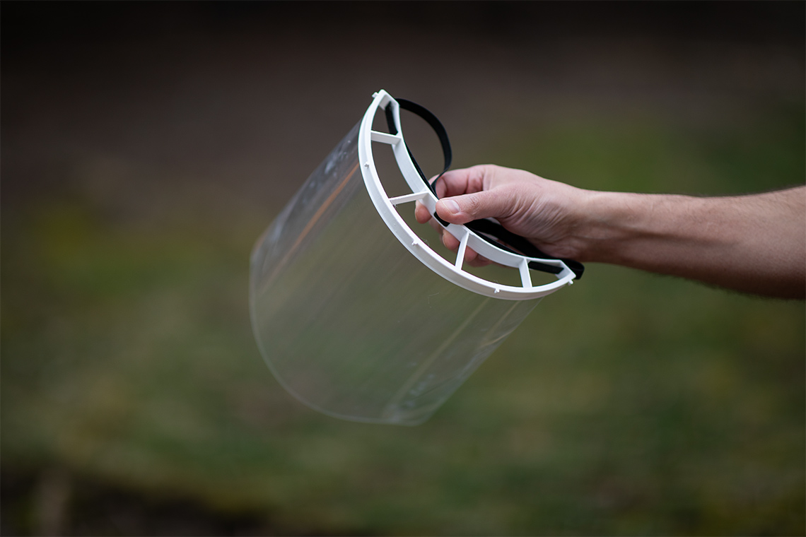 A reusable plastic face shield is held up on display