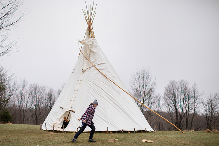 a woman walks past a teepee on a grey fall afternoon