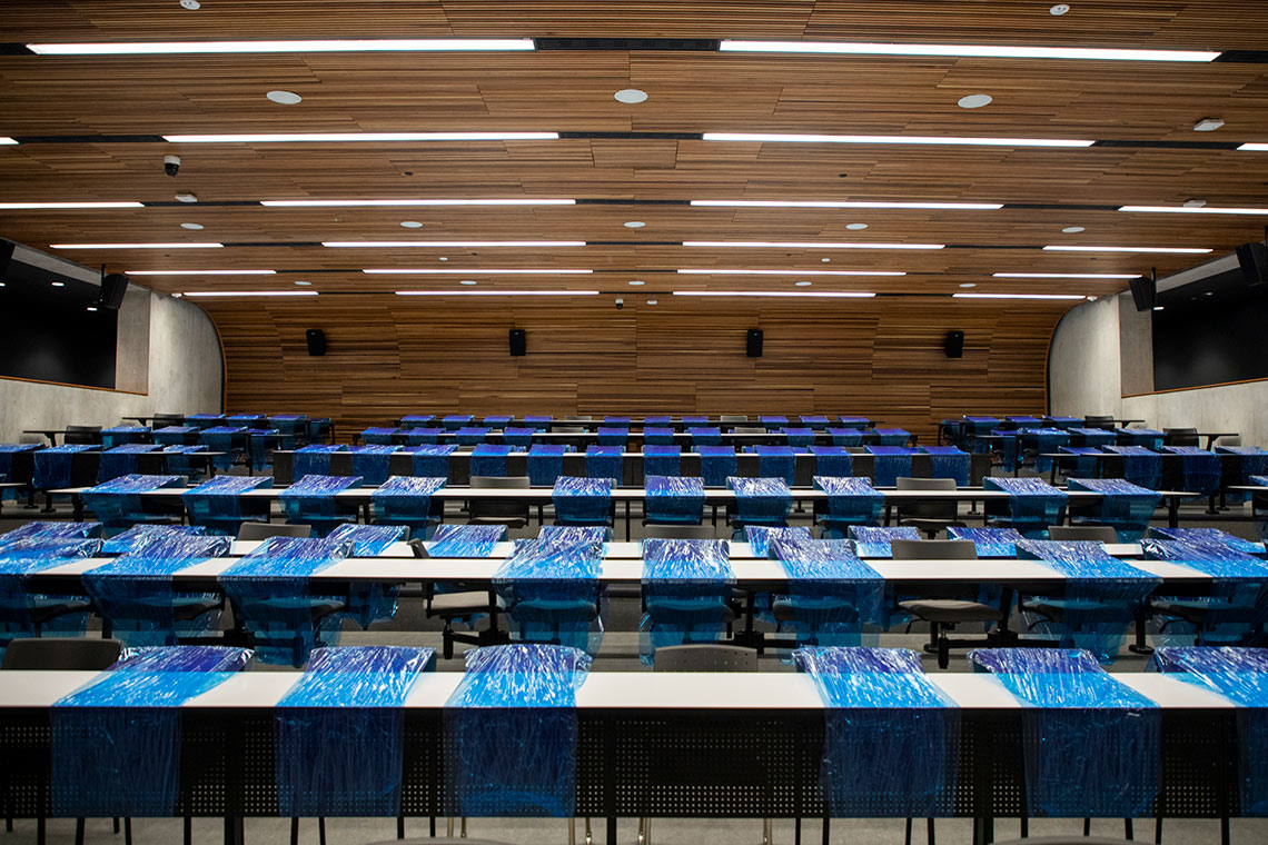 Shot of a lecture hall at U of T Mississauga with blue shrink wrap blocking off the majority of desks