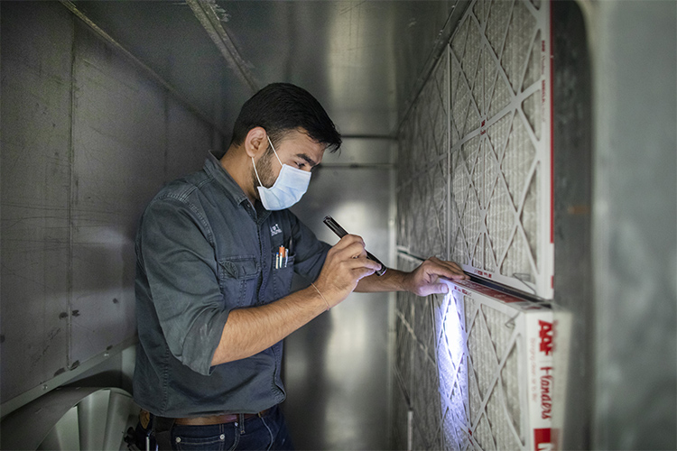 u of t staff check a building air filter at myhal