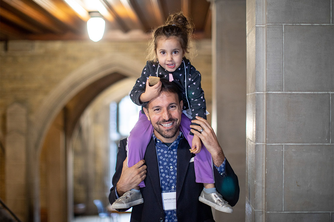 Portrait of Matthew Sergi with daughter Clio Glenn-Sergi on his shoulders
