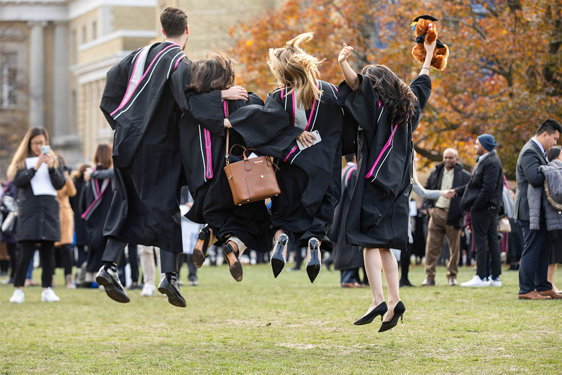 graduands jumping for joy in front of convocation hall
