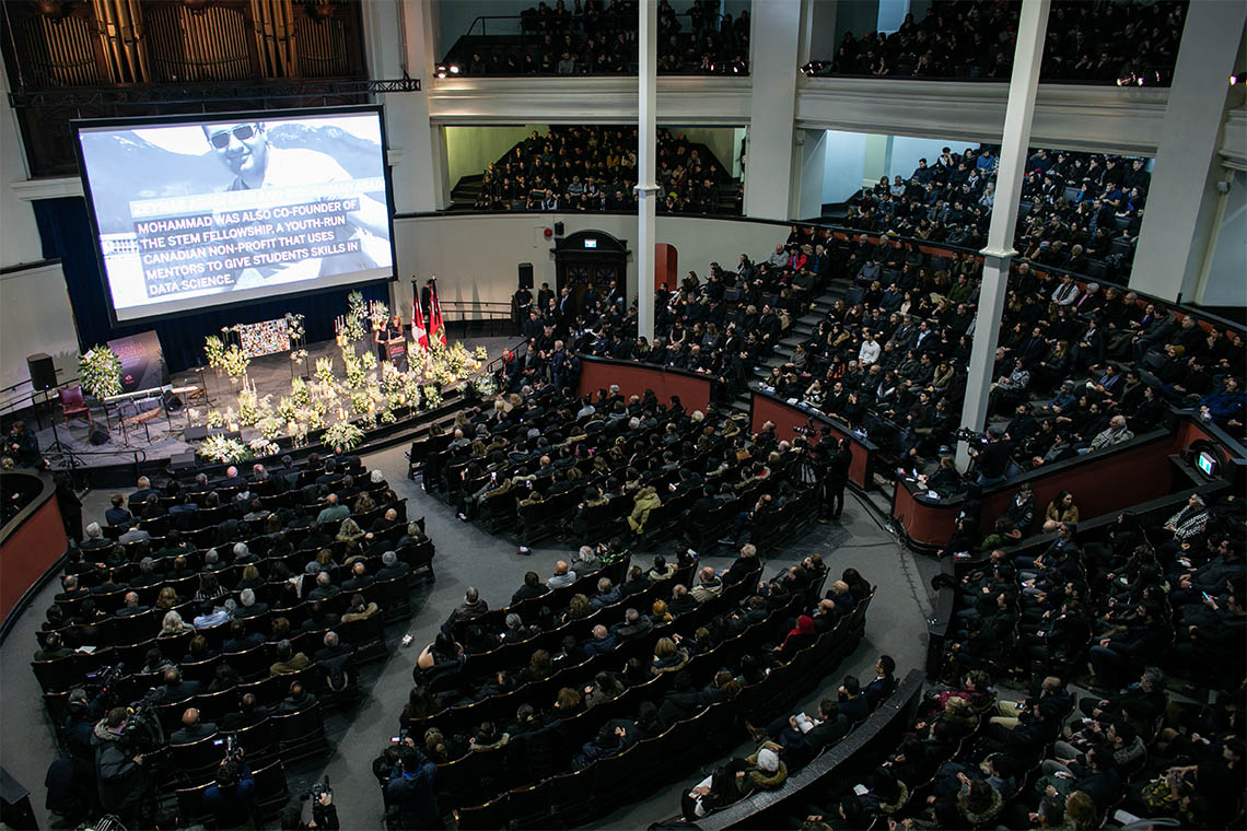 a wide view of the inside of a full convocation hall during the memorial