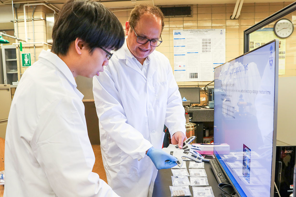 PhD candidate Yu-Chen (Gary) Sun and Professor Hani Naguib hold a glove made with smart materials in a laboratory