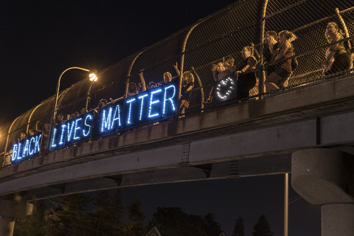 BLM supporters with a lit up Black Lives Matter sign on a bridge in Milwaukee
