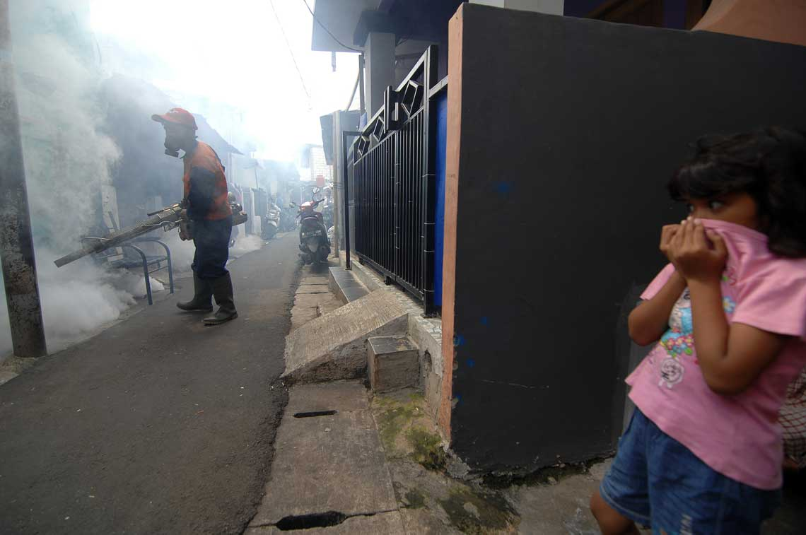 photo of little girl trying to avoid inhaling the spray for Zika-carrying mosquitos