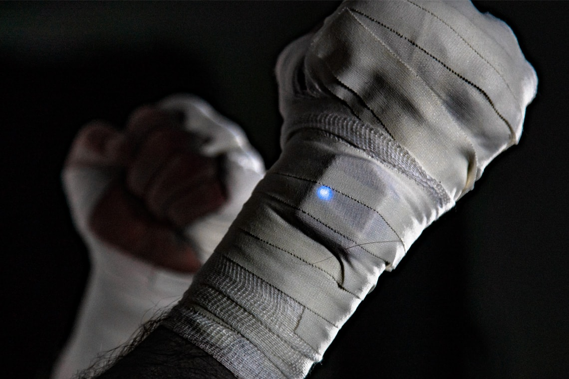 Photo of hands bandaged in fighting ready stance with wrist-mounted sensor
