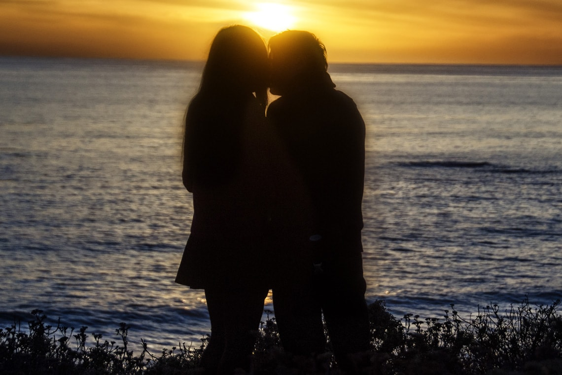 photo of a couple embracing by the water