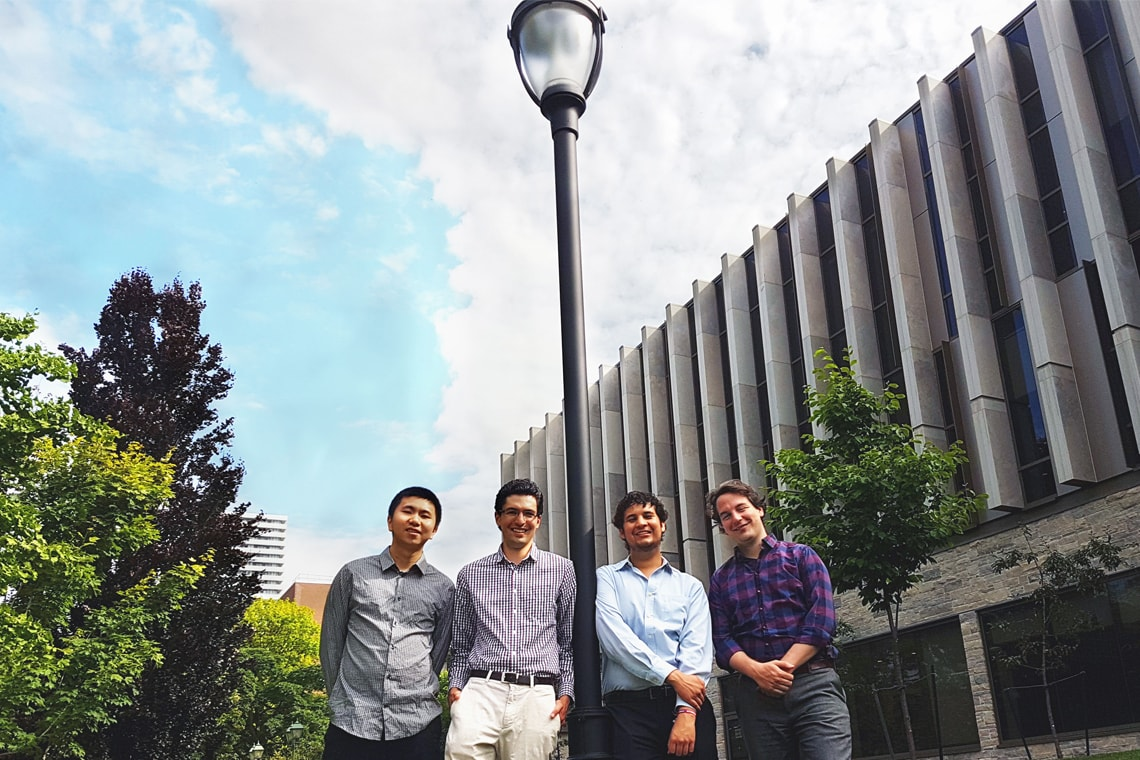 Photo of four engineering students standing by lamp post