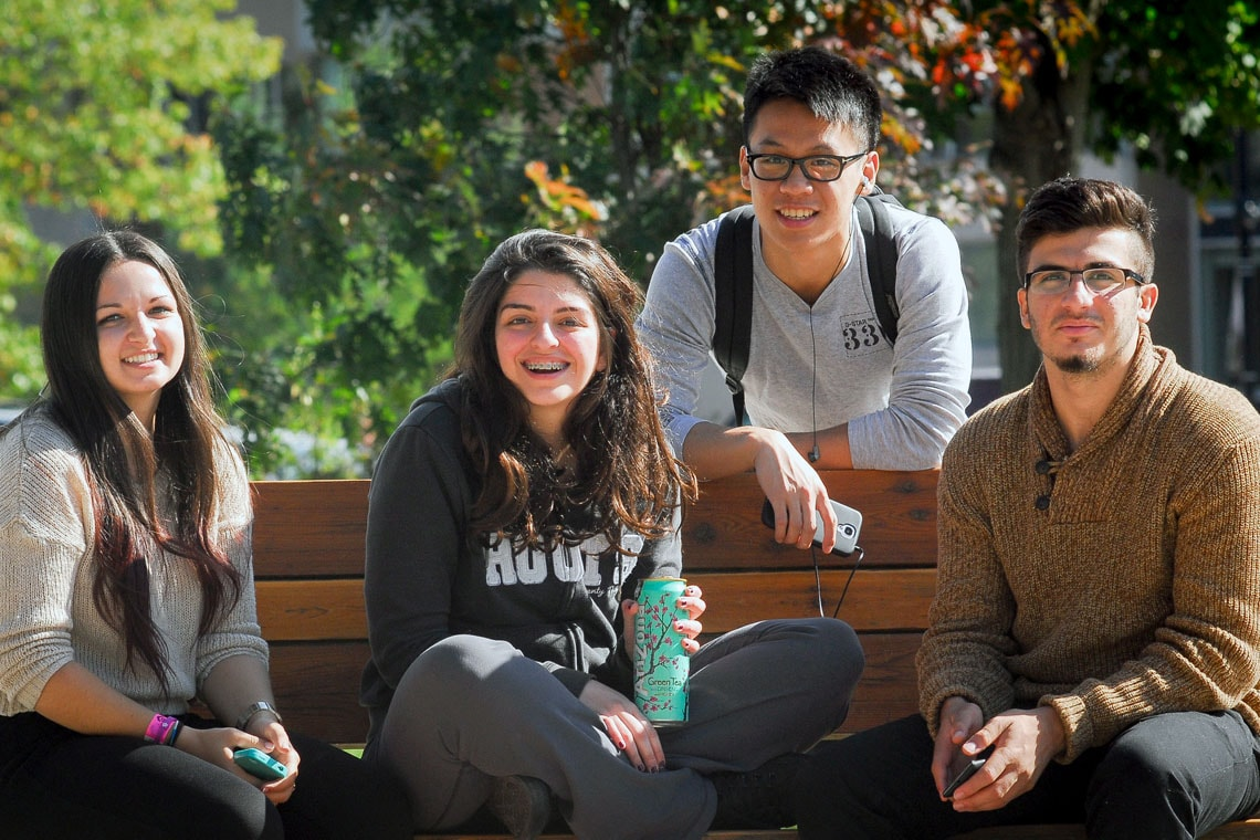 Photo of four students on bench