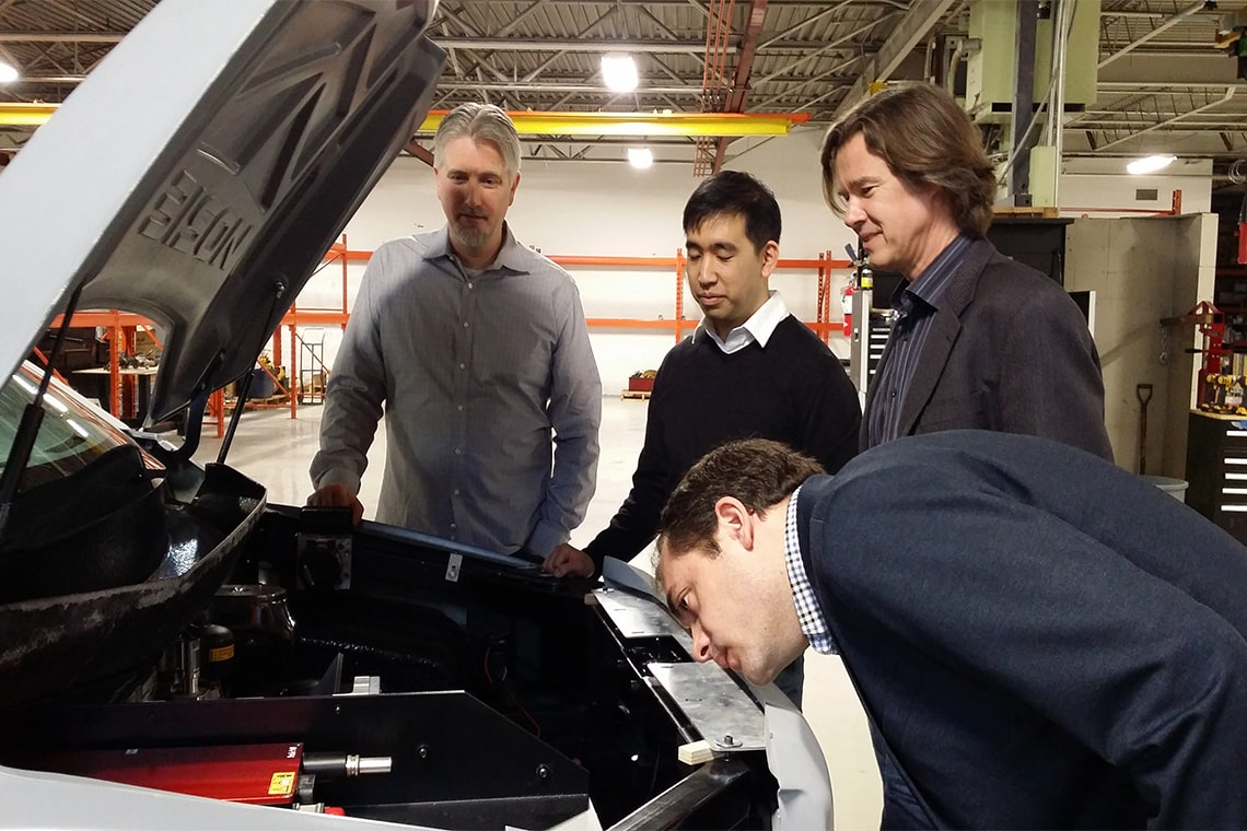 photo of researchers looking under the hood of car