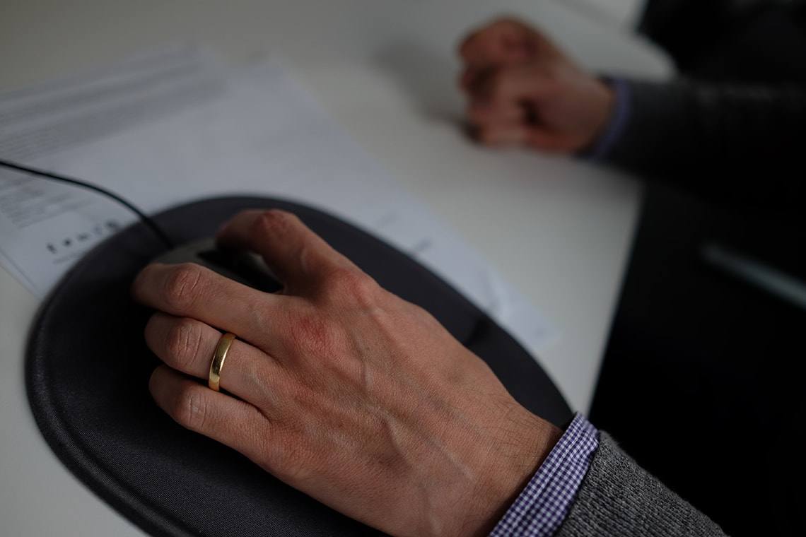 Hand with wedding ring in office