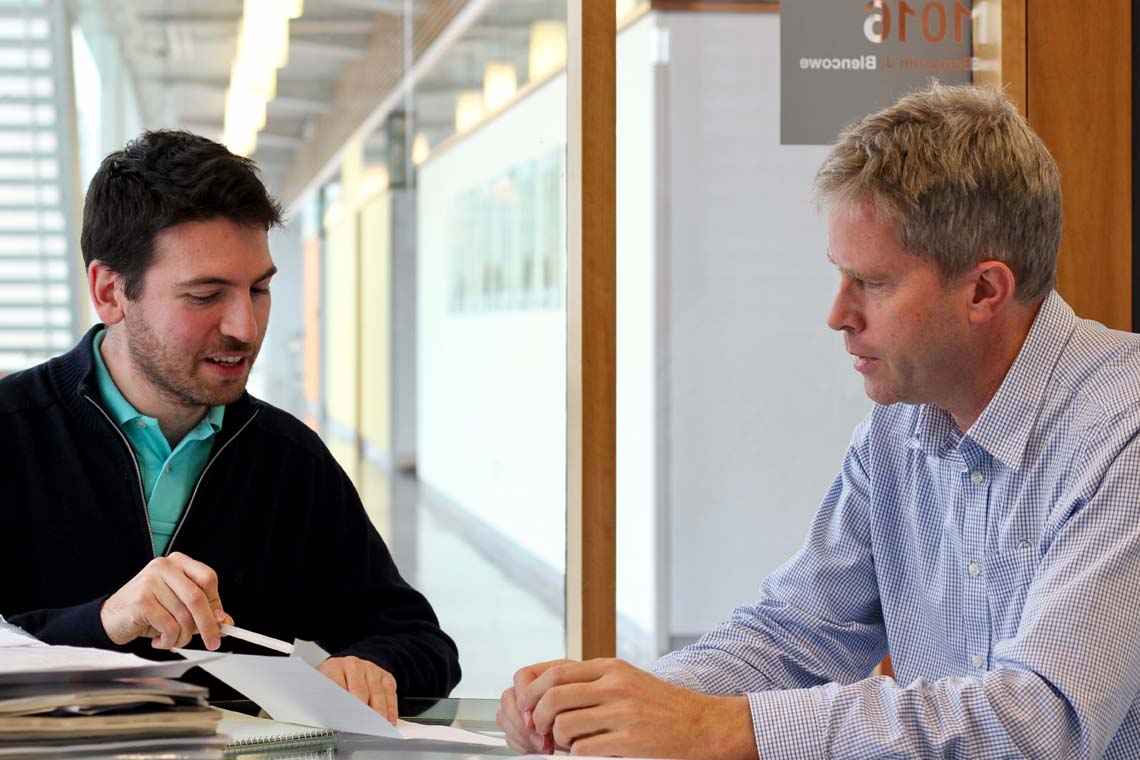 photo of Professor Blencowe and the lead researcher seated at a desk, reviewing study