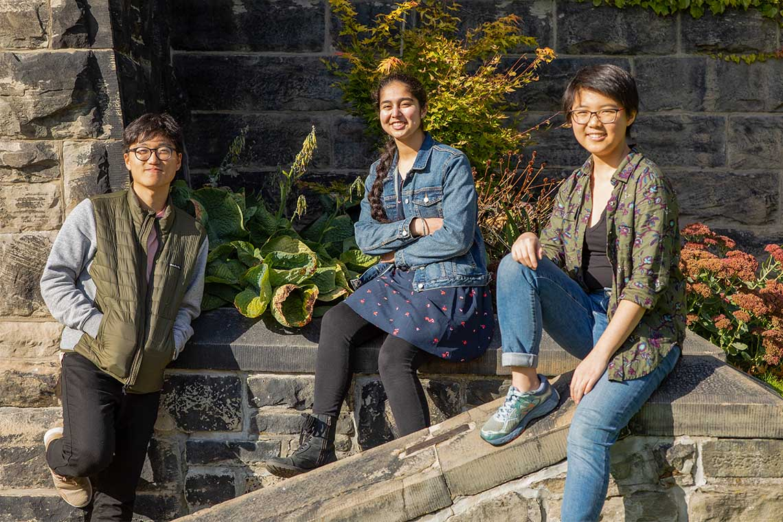 Chan-min Roh, Abnash Bassi and Shiqi Xu pose outside University College on a sunny fall day