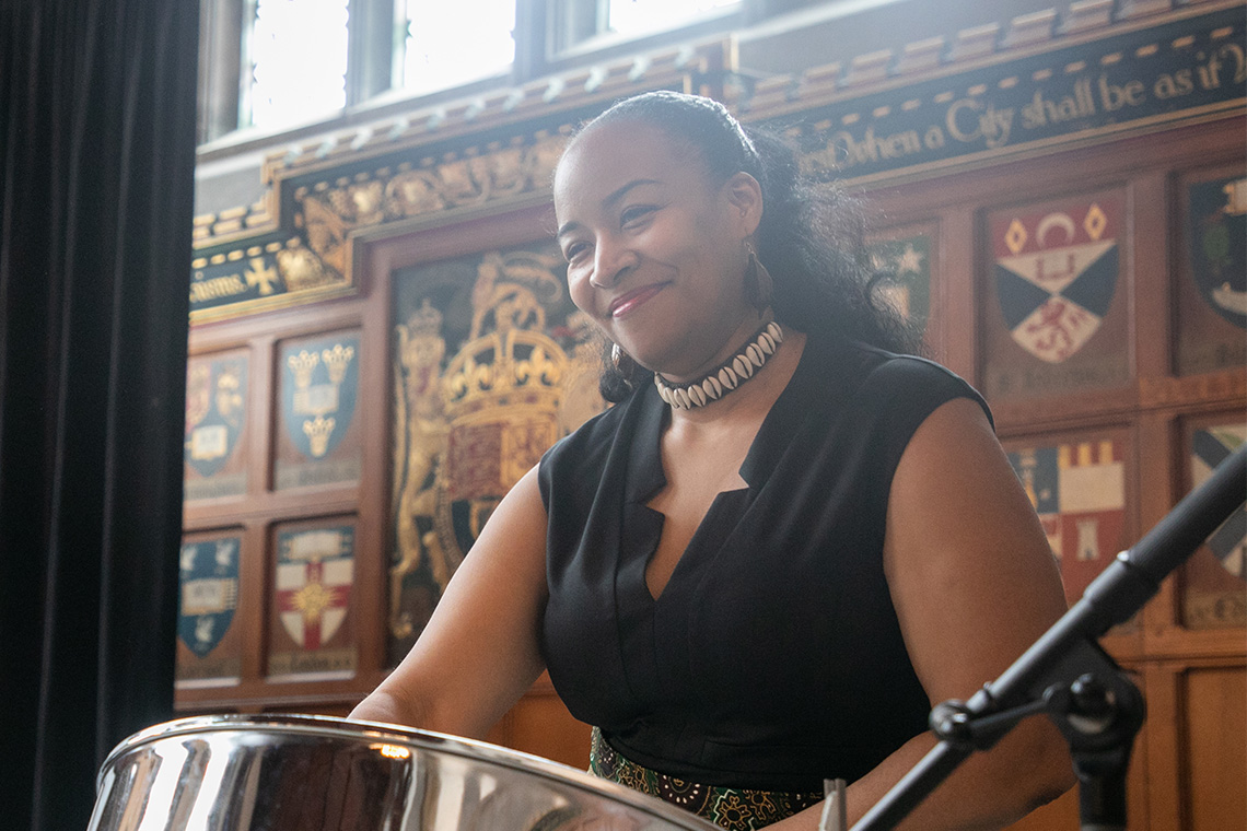 a woman play a steel drum at hart house black history month luncheon 2020