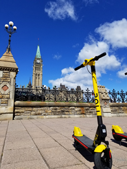 a roll scooter is parked outside parliament hill in ottawa