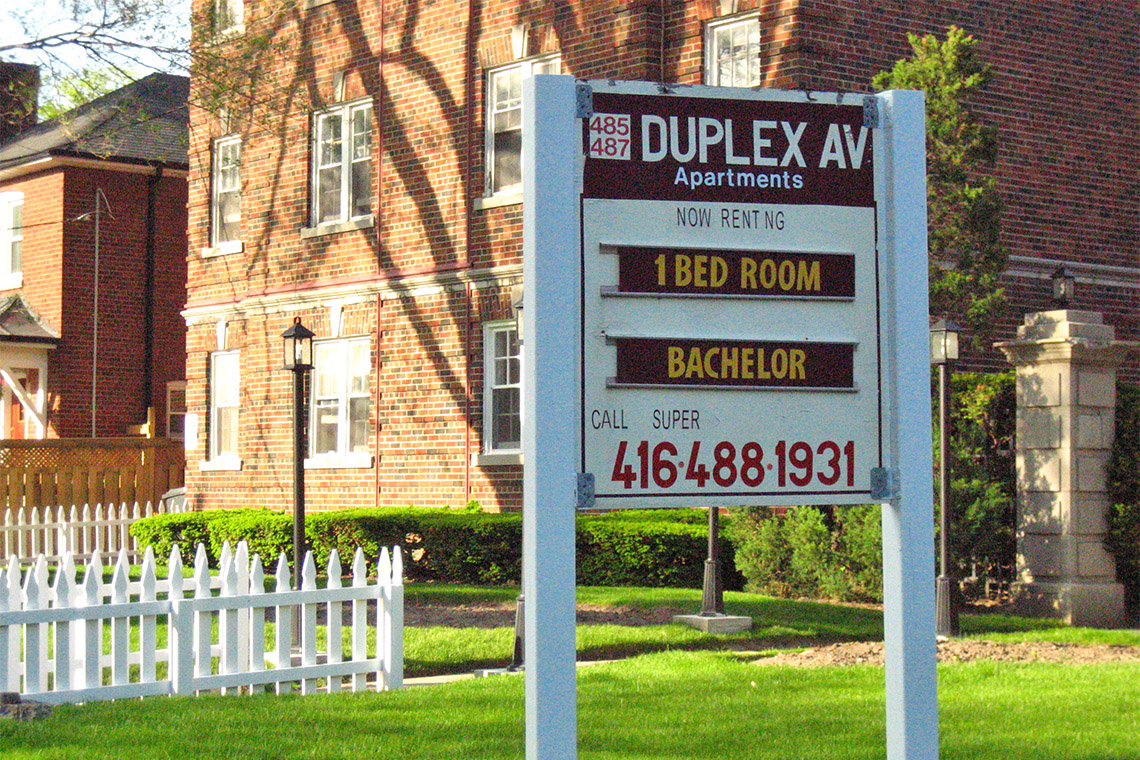 A wooden sign advertises apartments for rent in Toronto on Duplex avenue
