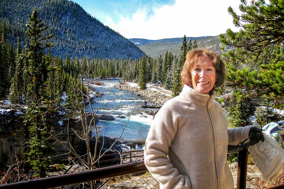 photo of Marilyn Smith with a river, mountains and trees in the background