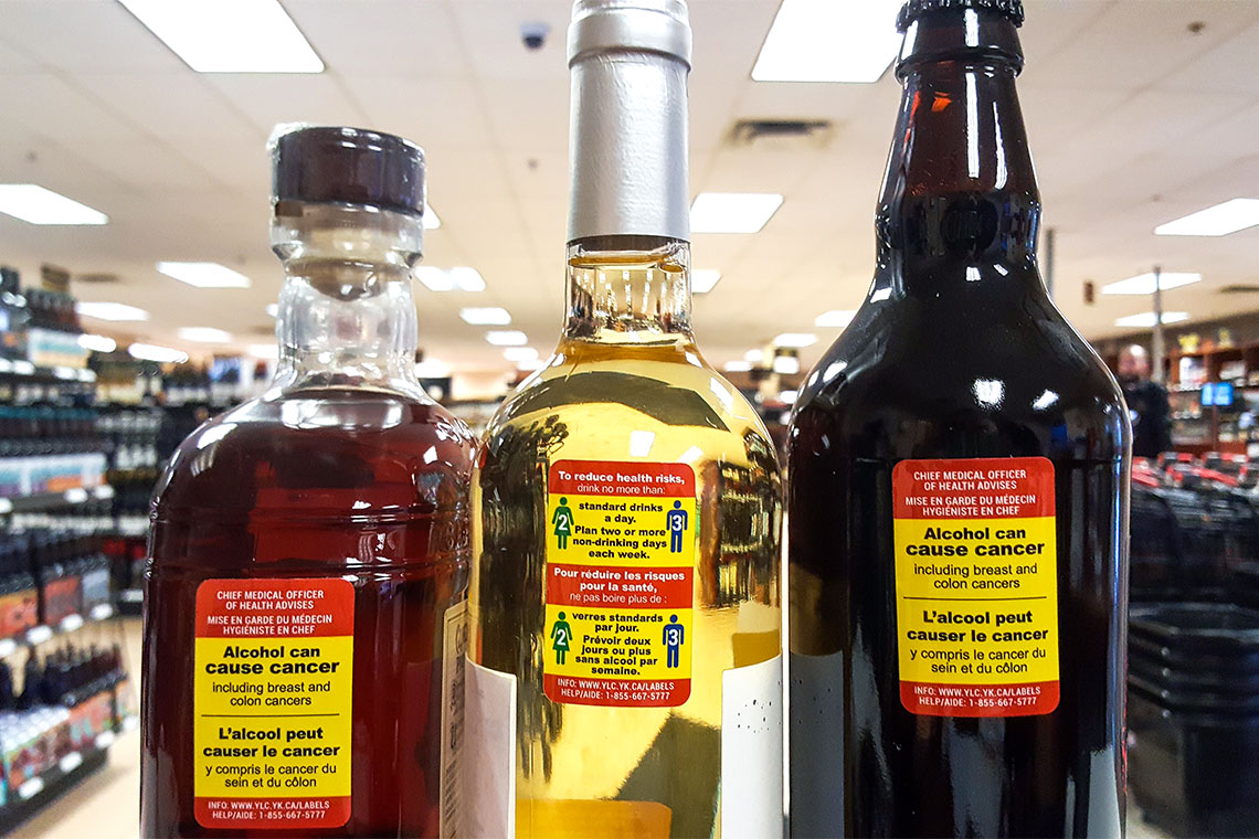 3 bottles of various types of alcohol at a Whitehorse liquor store with yellow and red health warning stickers