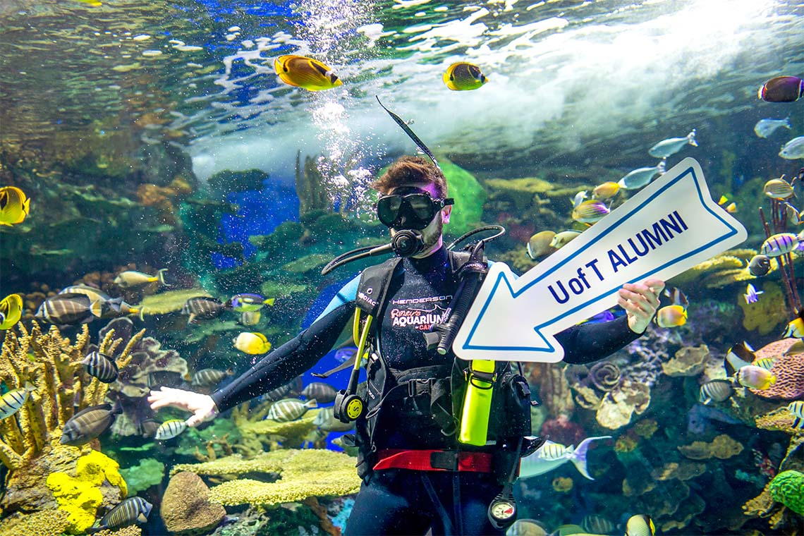 Scuba diver in the Ripely's Aquarium fish tank holding a U of T Alumni arrow directing guests to the party