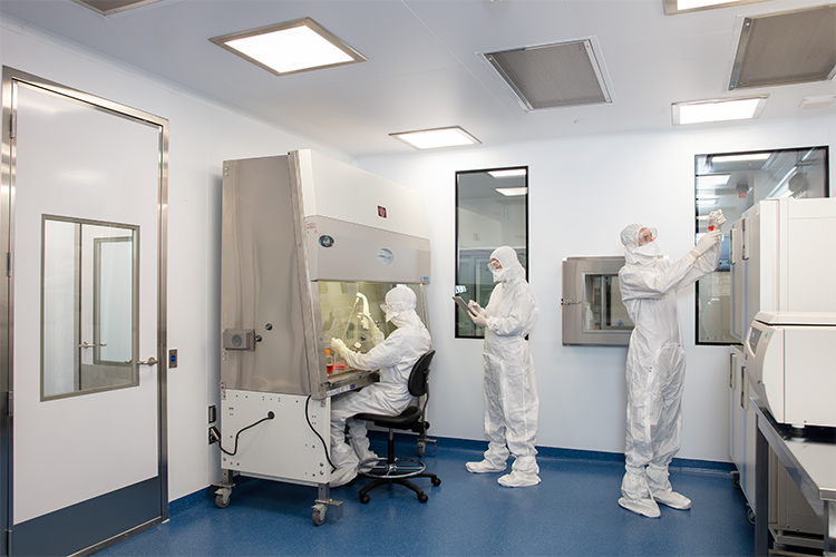 Workers demostrate the new CCRM lab in clean suits