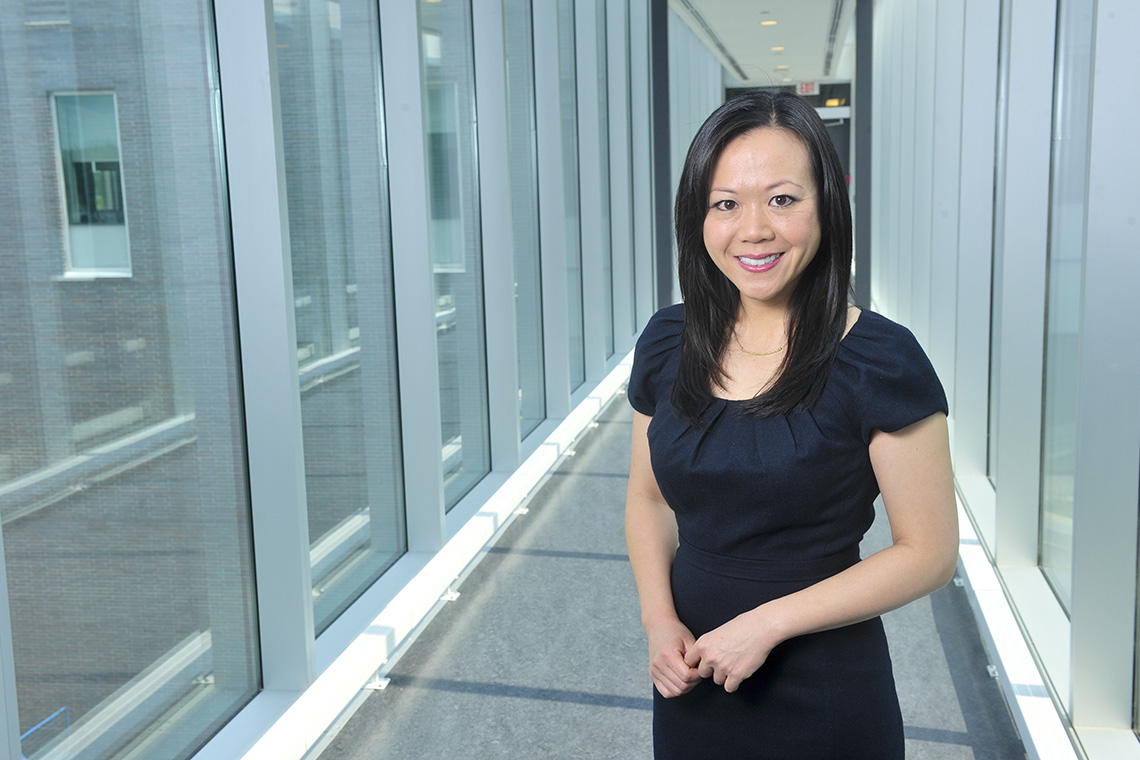 Photo of Cindy Chan standing in a glass hallway