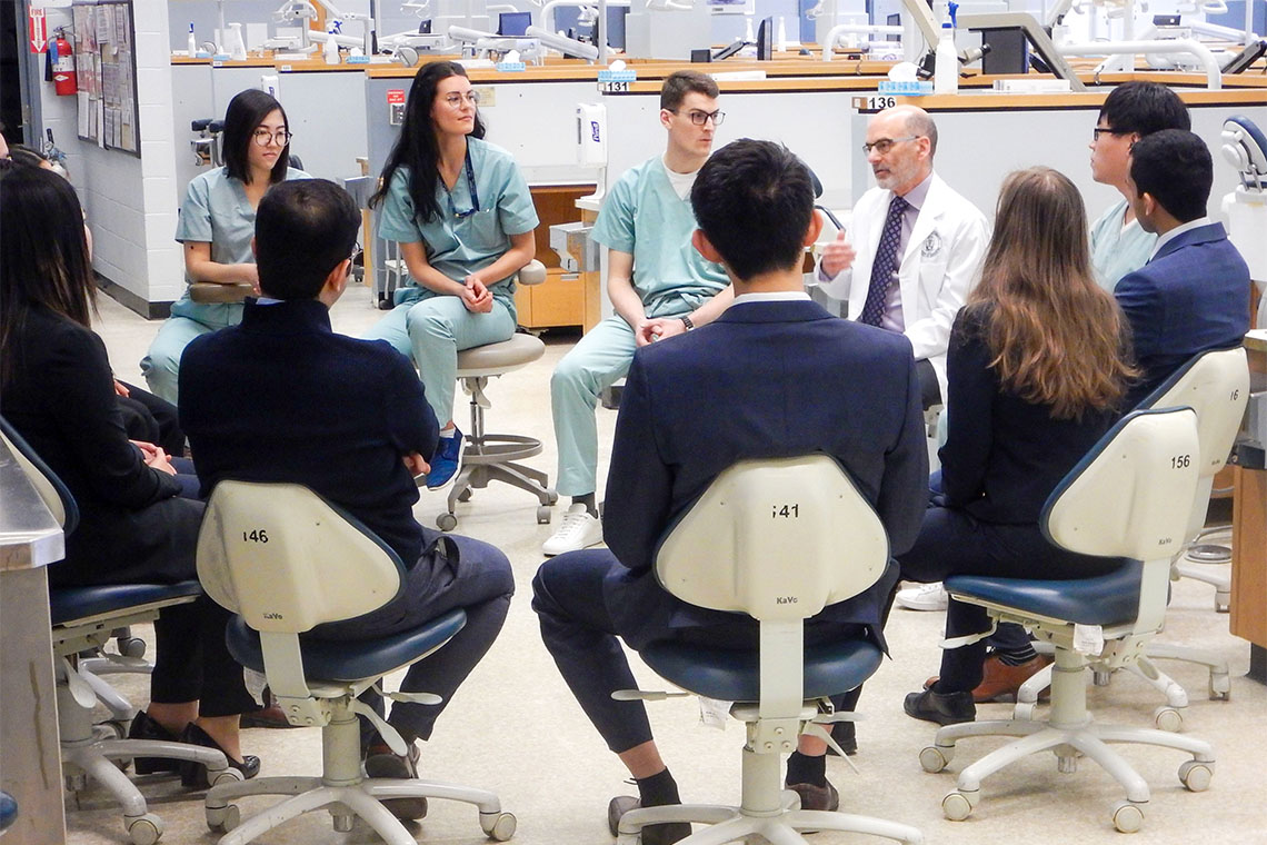 a group of students seated in chairs in  a dentistry classroom surround dean Daniel Haas