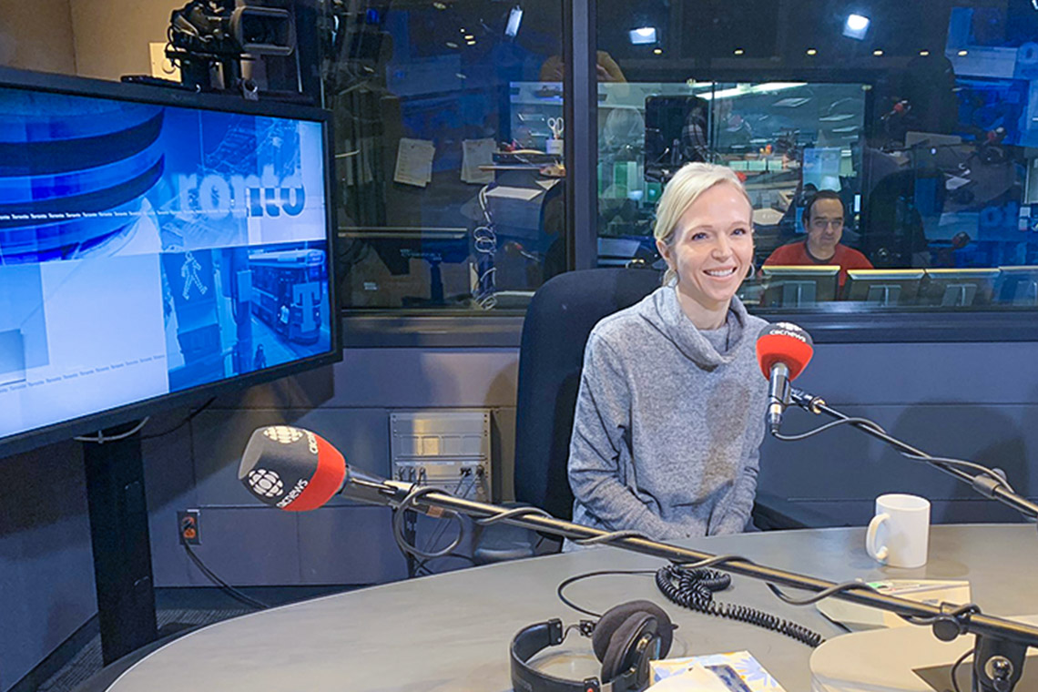 Christine Allen sits in front of a microphone in the CBC studio