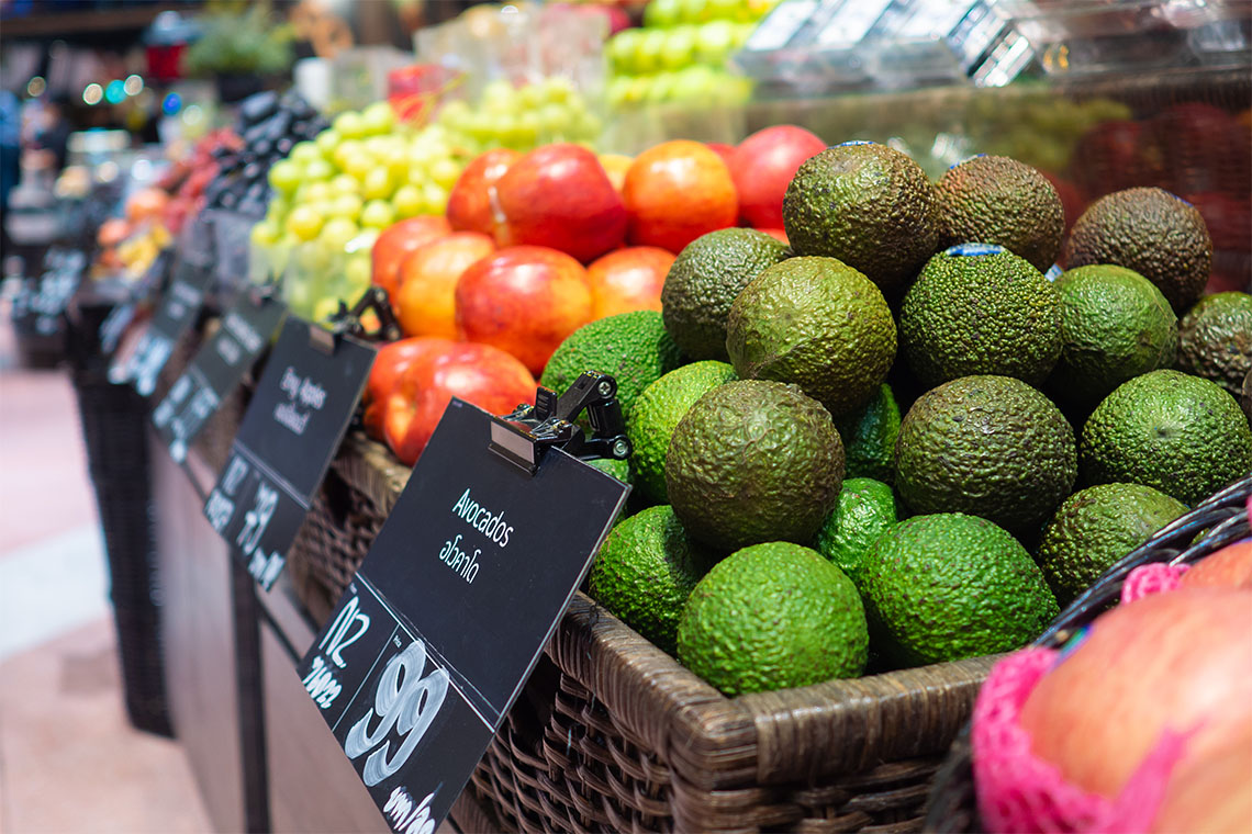 Avocados and tomatoes are piled high at a supermarket
