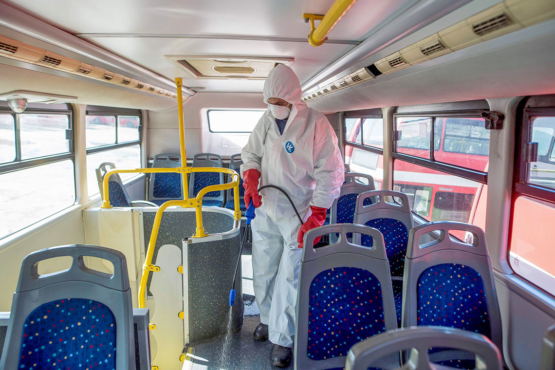a person dressed in protective equipment sprays disinfectant on a bus in Macedonia
