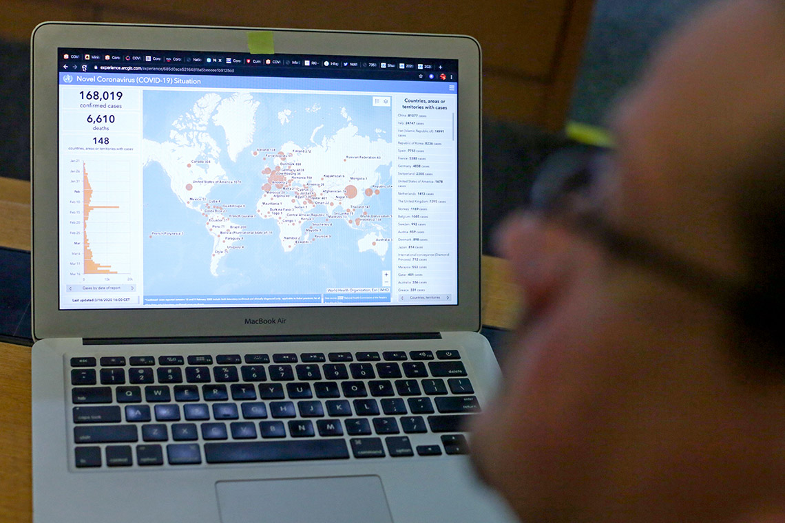 Photo of a laptop displaying a graphic of COVID-19 cases around the world