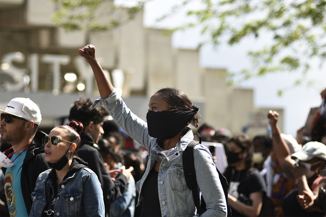 A young Black woman raises her fist in the air at a Black lives matter protest