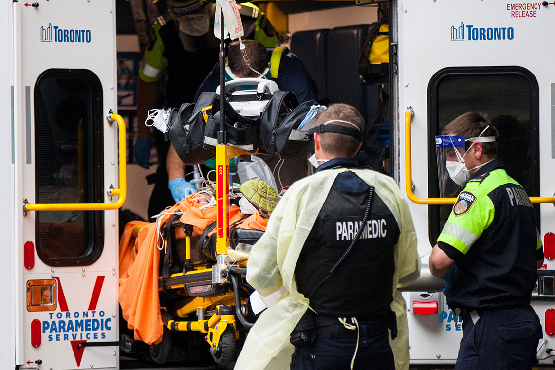 Toronto paramedics dressed in PPE take a patient out of an ambulance