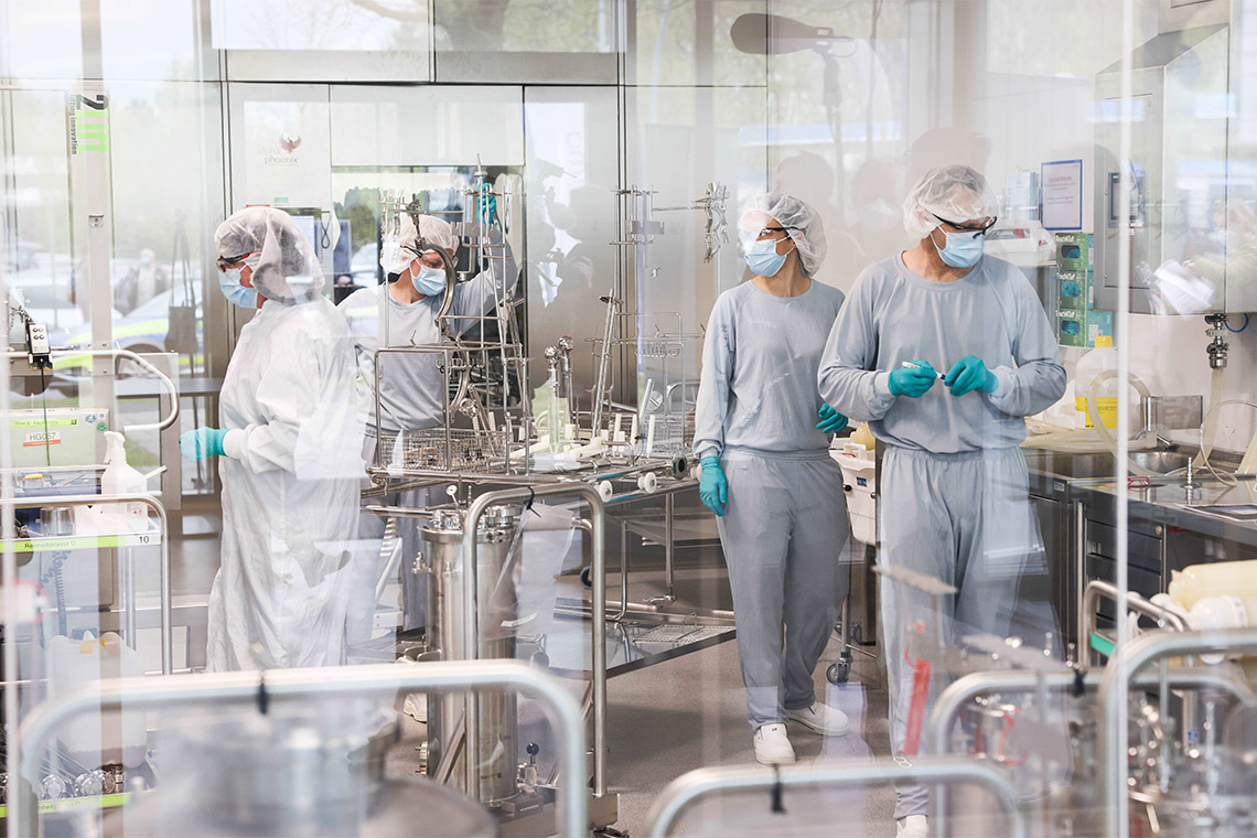 scientists in a cleanroom manufacturing vaccines