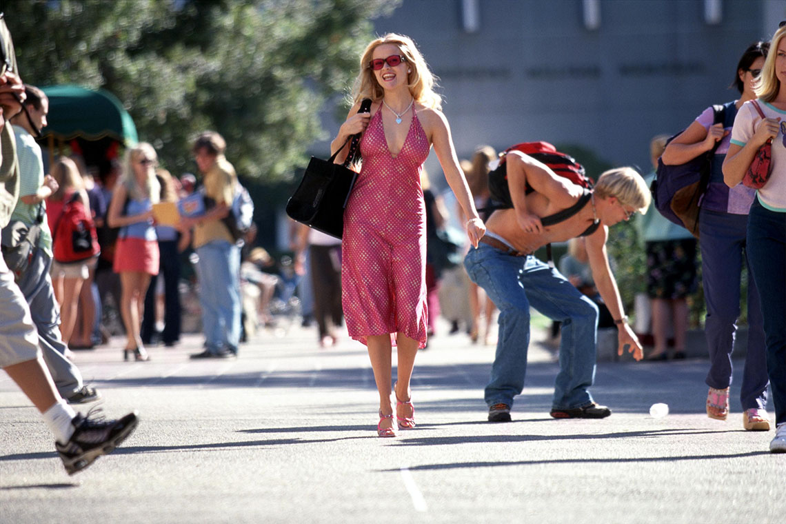 Reese Witherspoon as Elle Woods in the movie Legally Blonde. She is dressed in a bright pink dress and smiling while walking down the street.