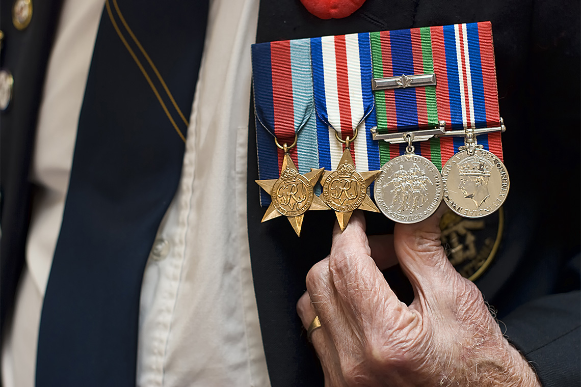 senior citizen wearing naval war medals