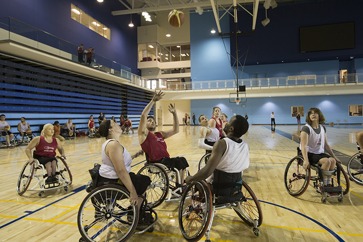 athletes in wheelchairs play a practice game of basketball at the pan am sports centre