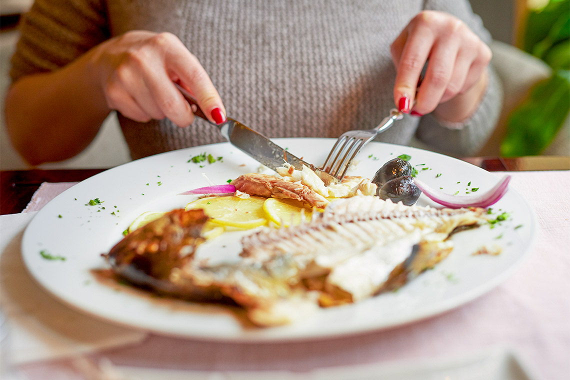 Woman eating fish in a restaurant