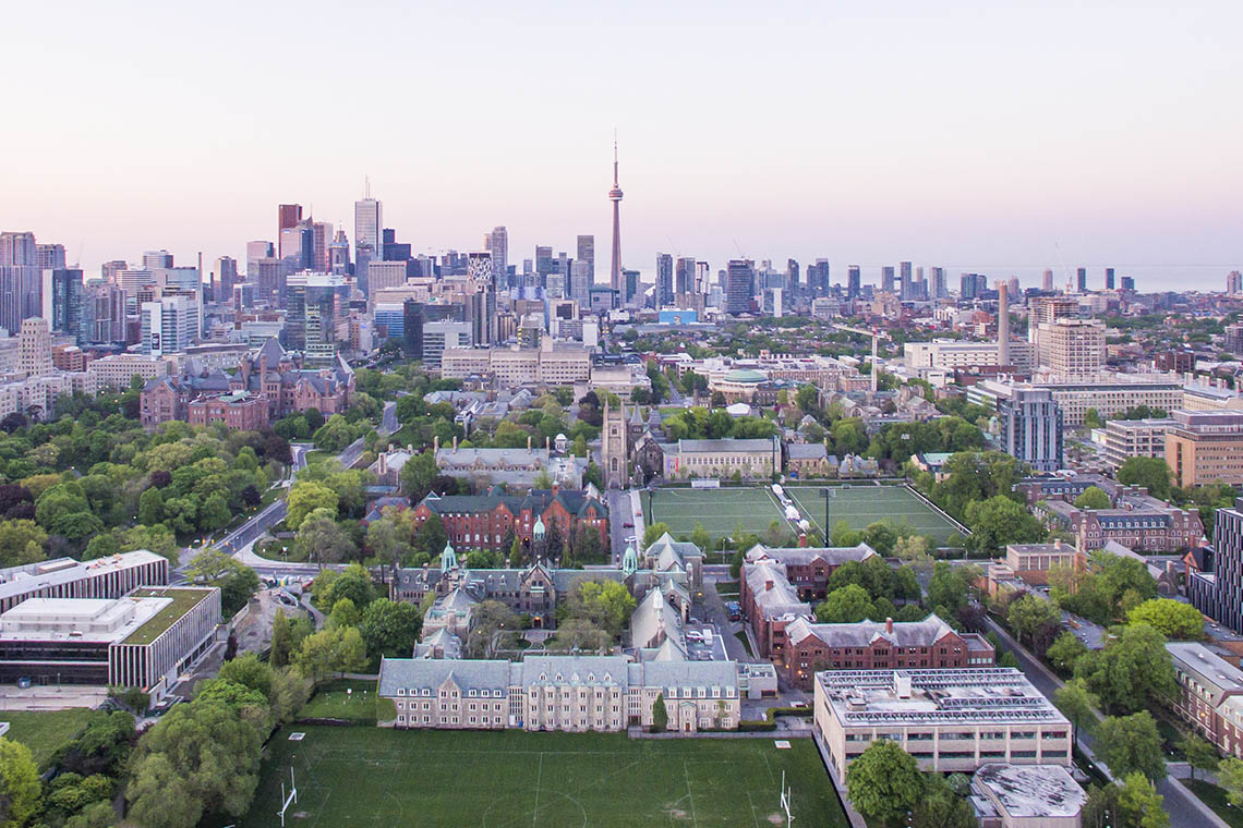 Aerial view of U of T downtown campus bathed in a rosy glow from the sun rising