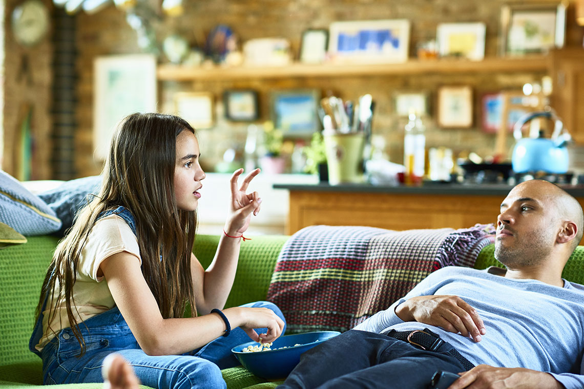 A father and daughter talking on a sofa