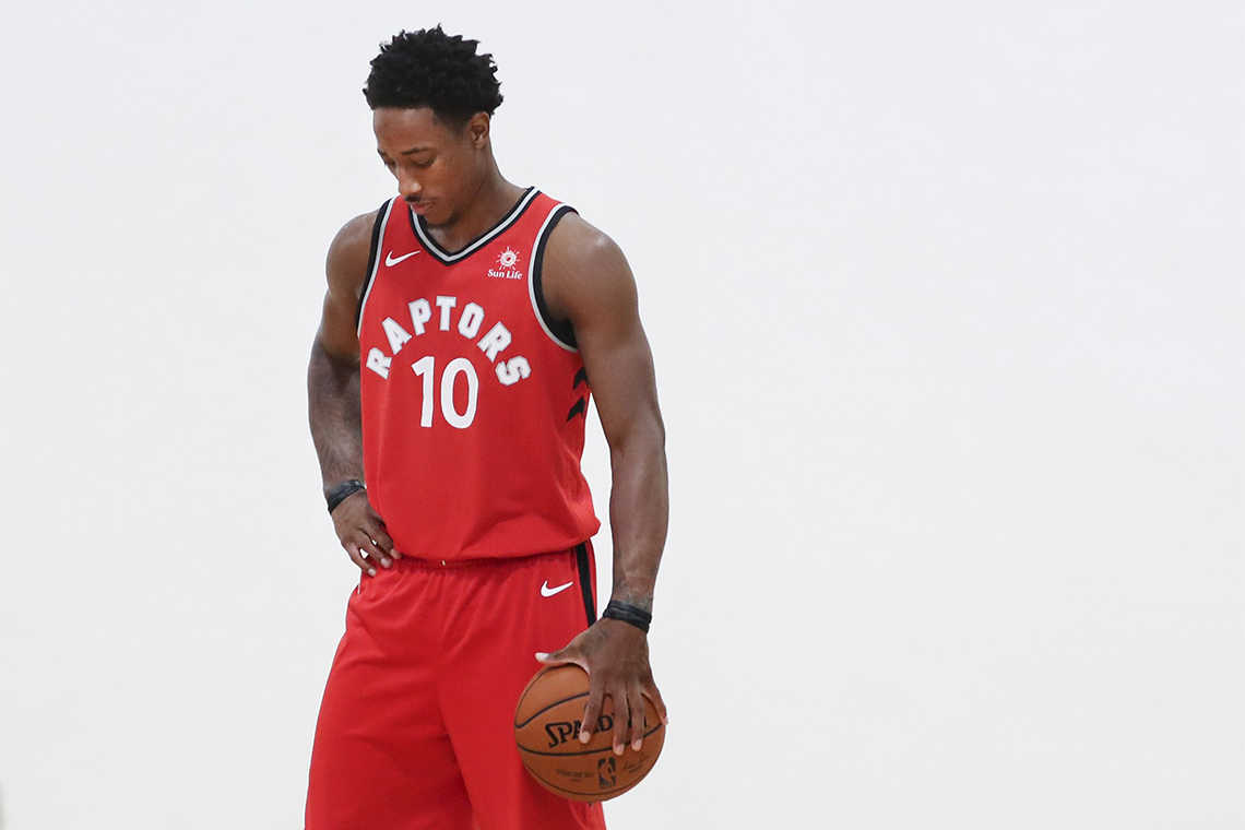DeMar DeRozan, in a red Raptors uniform, holds a basketball at his side