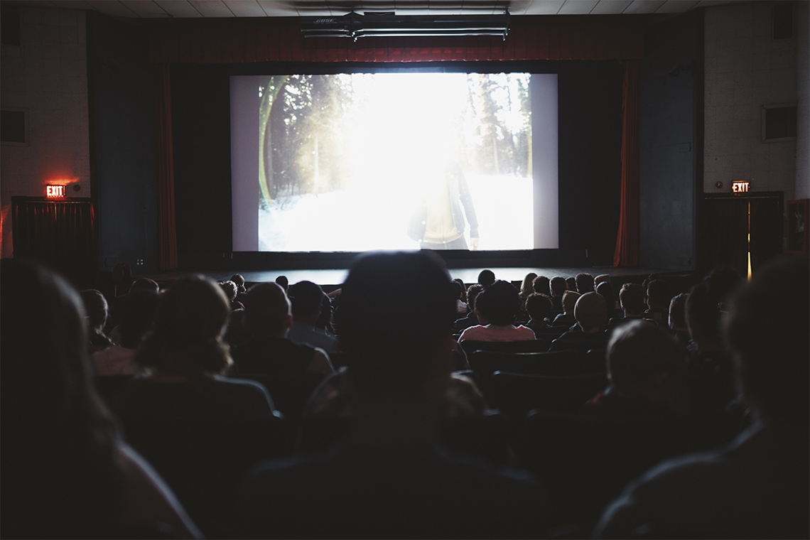 Stock photo of the backs of heads in a movie theatre