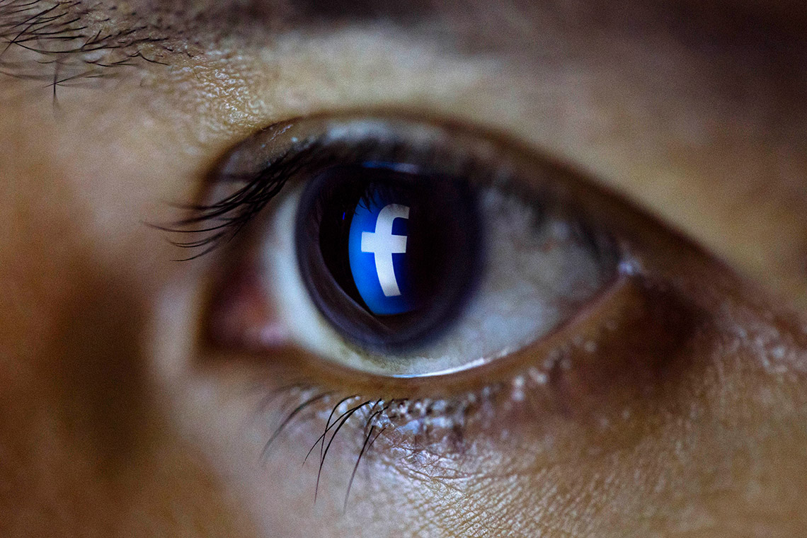 close up photo of a person's eye with the Facebook logo reflected in it