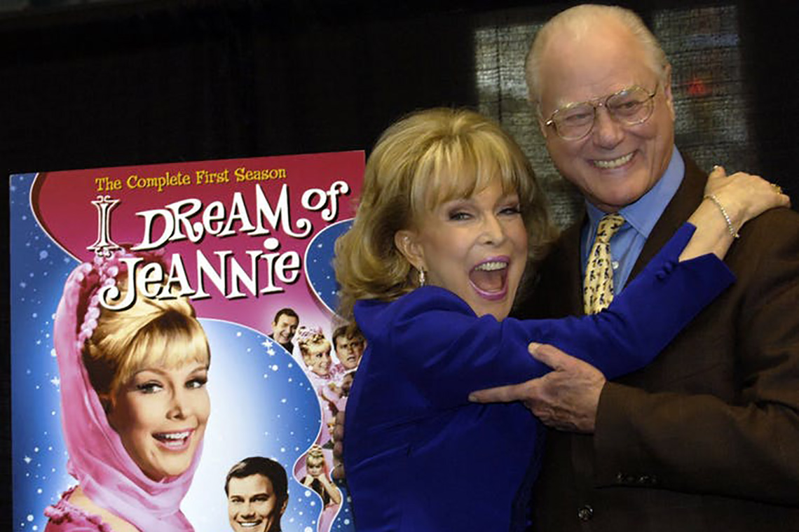 'I Dream of Jeannie' co-stars Barbara Eden and Larry Hagman share an embrace in front of a 'I Dream of Jeannie' poster