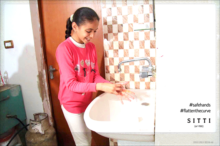 a young girl washes her hands with sitti soap