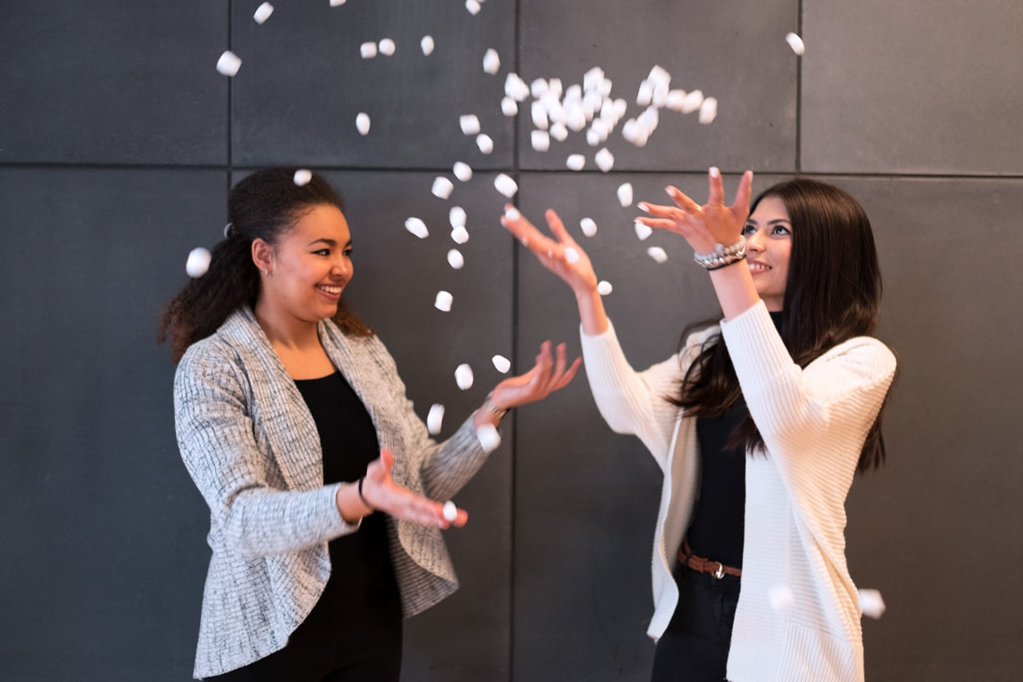 Students and Enactus U of T members Anne Ageh and Nuha Siddiqui toss prototypes of EcoPacker's eco-friendly packing peanuts in the air