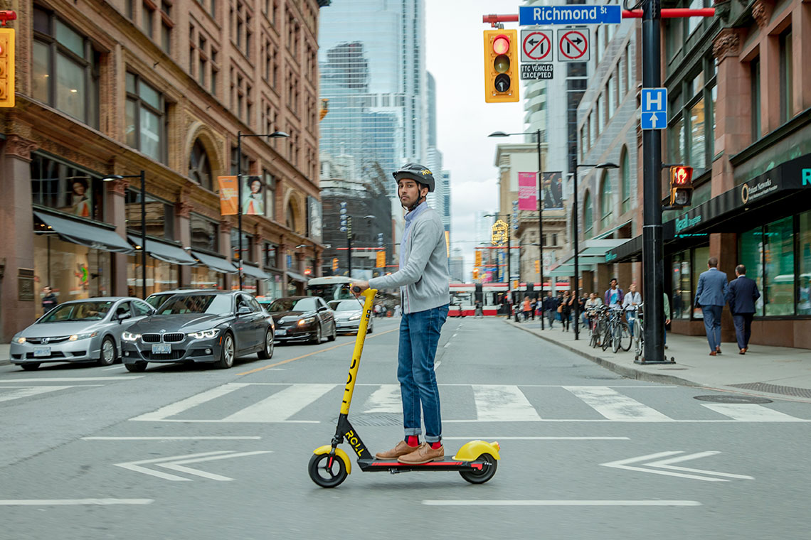 man rides a roll electric scooter in downtown toronto